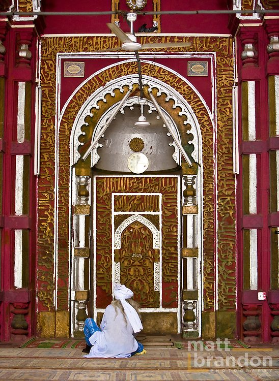 A faquir, or Islamic sadu of sorts, sits and reads the Qu'ran at the quibla of the Allauddin Masjid, Nizamuddin, Delhi. Thi sis one of the oldest mosques built in India.