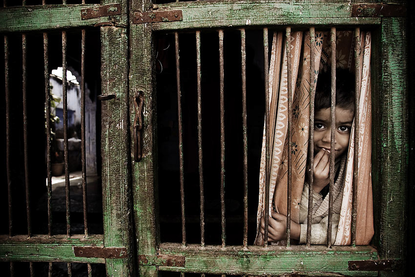 A young indian boy looks through the main gate of an orphanage in Bundi, a small village in Rajasthan, India.