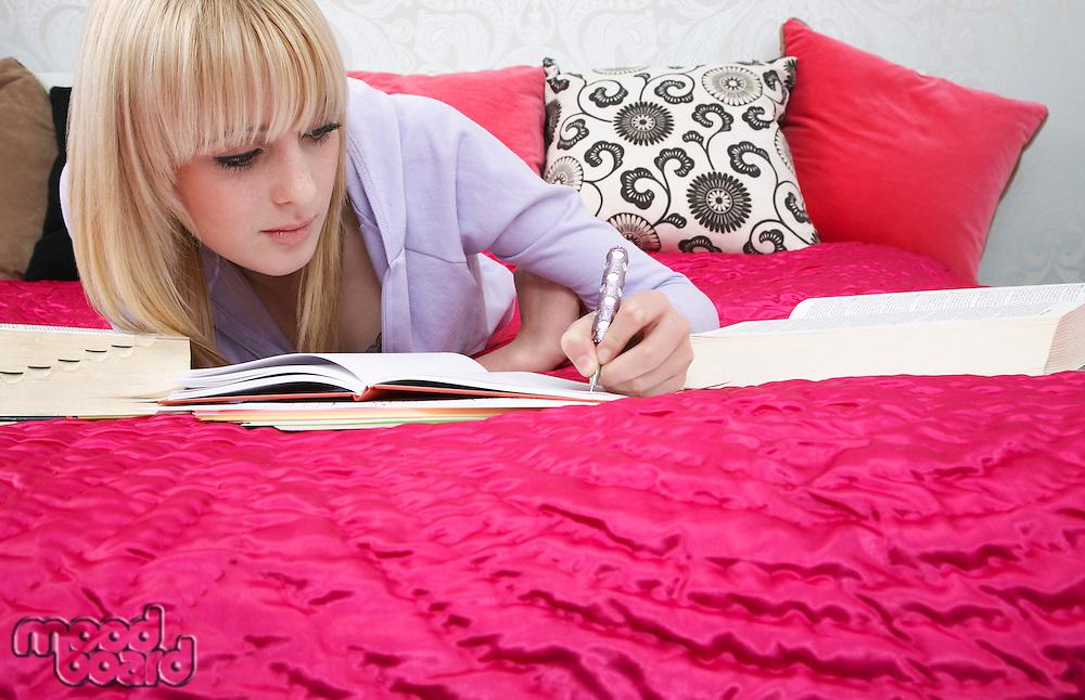 Teenage girl (16-17) lying on bed writing
