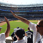 Fans young and old celebrate a Yankees run scored during the New York Yankees V Cincinnati Reds Baseball game at Yankee Stadium, The Bronx, New York. 19th May 2012. Photo Tim Clayton