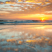 Sunrise lights the sky and reflects along the wet sands of Cape Hatteras National Seashore in the Outer Banks of North Carolina.  Cape Hatteras National Seashore is a chain of barrier islands on the coast of North Carolina.