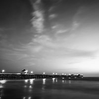Black and white photo of San Clemente pier at sunset. San Clemente California is a costal city along the Pacific Ocean in the United States of America. Photo is high resolution. Copyright ⓒ 2017 Paul Velgos with All Rights Reserved.