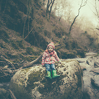 A young girl wearing a flowery raincoat sitting alone on a rock beside a stream in woodland in winter