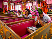 "14 FEBRUARY 2018 - BANG KRUAI, NONTHABURI, THAILAND: People in coffins participate in a resurrection ceremony at Wat Ta Khien, about 45 minutes from Bangkok in Nonthaburi province. The temple is famous for the ""floating market"" on the canal that runs past the temple and for the ""resurrection ceremonies"" conducted by monks at the temple. People lie in a coffin and ritualistically die before being reborn. Adherents believe it will improve their karma and help make up for past sins.         PHOTO BY JACK KURTZ"