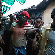 People carry a wounded man who witnesses said was injured in clashes between Hausa locals and Biafran protesters in Port Harcourt, Nigeria, Tuesday Nov. 10, 2015. Witnesses said the riot broke out when Biafran protesters had an altercation with locals in a Hausa neighborhood of Port Harcourt. Jesse WInter Photo.