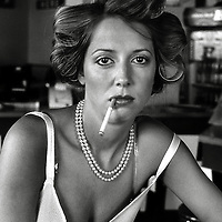 A young woman with rollers in her hair smoking a cigarette