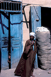 Esna, Egypt:  Street scene. Note cotton bale, and person peeking out from door.