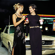Editorial photograph of two high fashion models that are enjyoying their burger and fries with a classic mustang. When we produced this job, we asked a patron at the diner, if we could borrow his vintage car for out fashion shot.