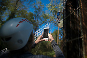 Pamela Gaboury takes a photo of Dean Gaboury climbing up the ziplining tower at the Challenge Course at The Ridges. Photo by Hannah Ruhoff