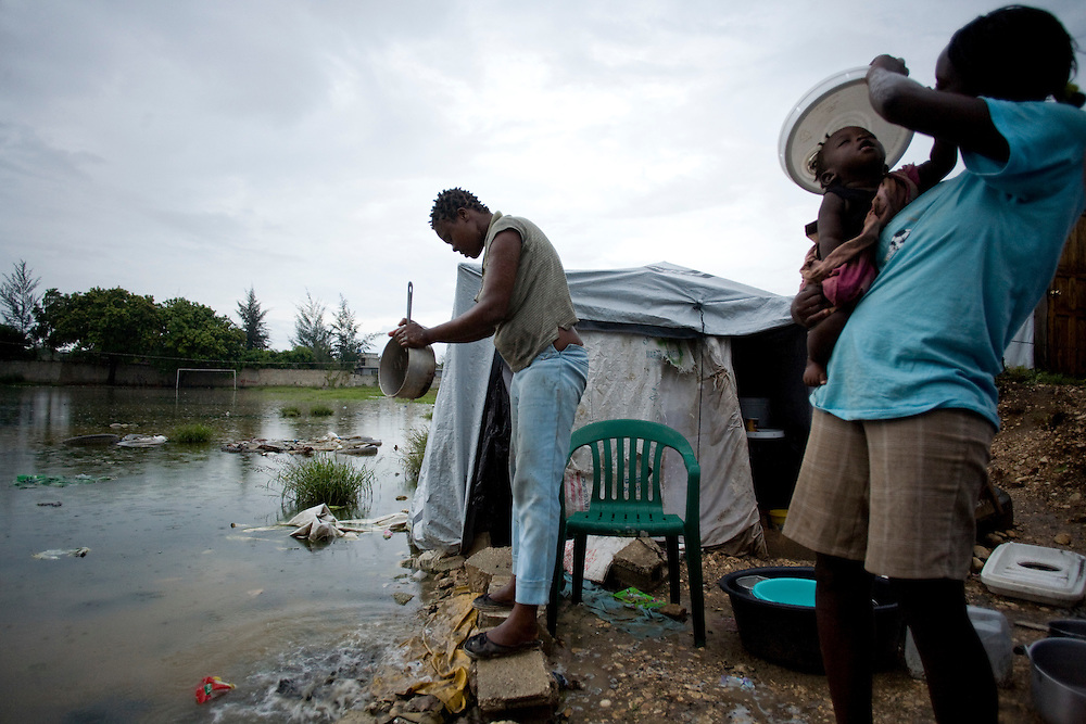 Gislene St. Jean, left, washes dishes into the pond encroaching on her tent. Roseline Mathieu holds a bucket lid over her 8 month old son Mavins to protect him from the rain.