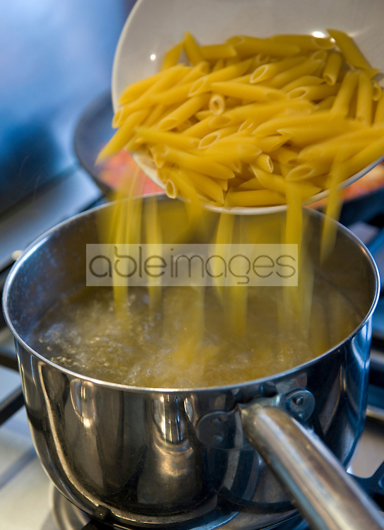 Dropping penne pasta into a pot of boiling water