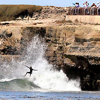 A surfer catches a wave at the legendary Steamer Lane break in Santa Cruz, Califonria on July 2, 2007 as spectators watch from atop the Lighthouse Point cliff.