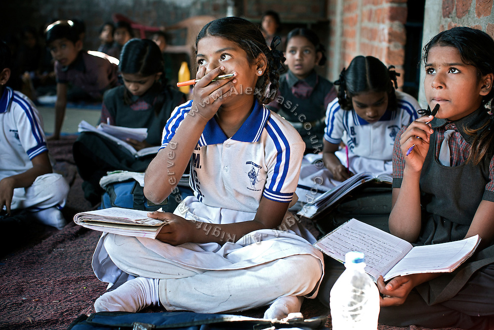 Alongside other pupils and her older sister Jyoti, 12, (back/right) Poonam, 11, (centre) is sitting of the floor during a lesson at a cozy, private school located by their newly built home, in Oriya Basti, one of the water-contaminated colonies in Bhopal, central India, near the abandoned Union Carbide (now DOW Chemical) industrial complex, site of the infamous '1984 Gas Disaster'.