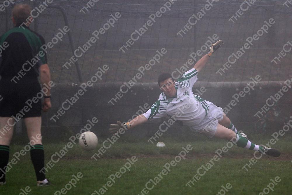 "Kilrush Shamrocks keeper Thomas Moloney is beaten from the penalty spot in the Bord na nÓg Football Minor ""B"" final against Corofin. - Photograph by Flann Howard"