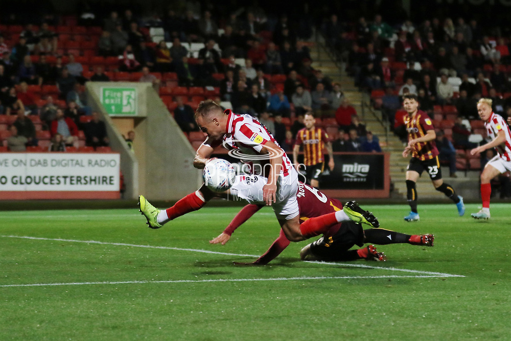 Luke Varney is tackled by Anthony O'Connor  during the EFL Sky Bet League 2 match between Cheltenham Town and Bradford City at Jonny Rocks Stadium, Cheltenham, England on 17 September 2019.