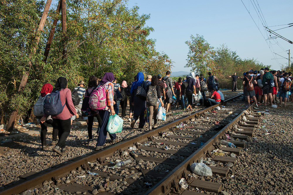 Refugees crossing the border to the Republic of Macedonia by following the train tracks. Busses come regularly to pick them up after they cross. <br /> Refugees arrive at Eidomeni border by bus and some times on foot. There they can cross to the republic of Macedonia on foot.