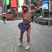 """Street performer Robert John Burck, known as The Naked Cowboy, wears a mask as he poses for photos in New York's Times Square, on Friday, May 8, 2020 during the coronavirus epidemic in New York City. He is wearing a mask and his guitar is adorned with stickers that read, """"Trump Keep America Great."""" (Alex Menendez via AP)"""