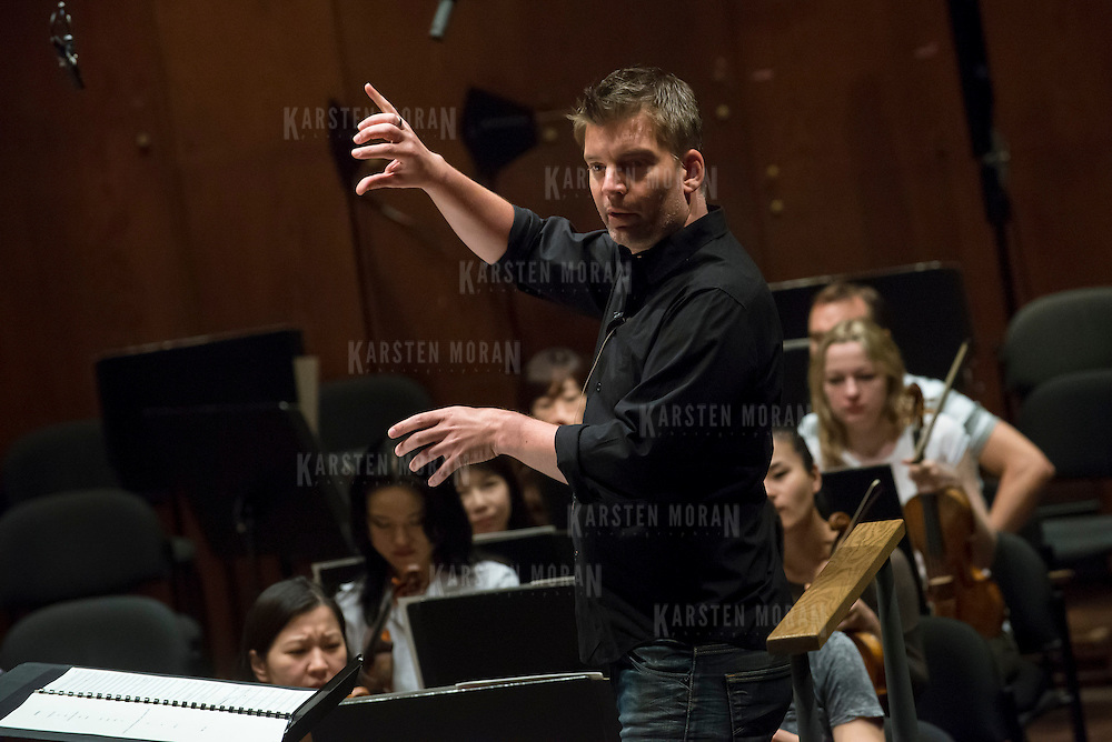 June 3, 2014 - New York, NY : Composer-conductor Matthias Pintscher, standing at center, works with the New York Philharmonic as they rehearse a piece by an up-and-coming composer at Avery Fisher Hall on Tuesday. Works by three little-known composers (one each) will be selected for inclusion in the New York Philharmonic's Biennial. CREDIT: Karsten Moran for The New York Times