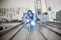 Young male worker welding in metal workshop