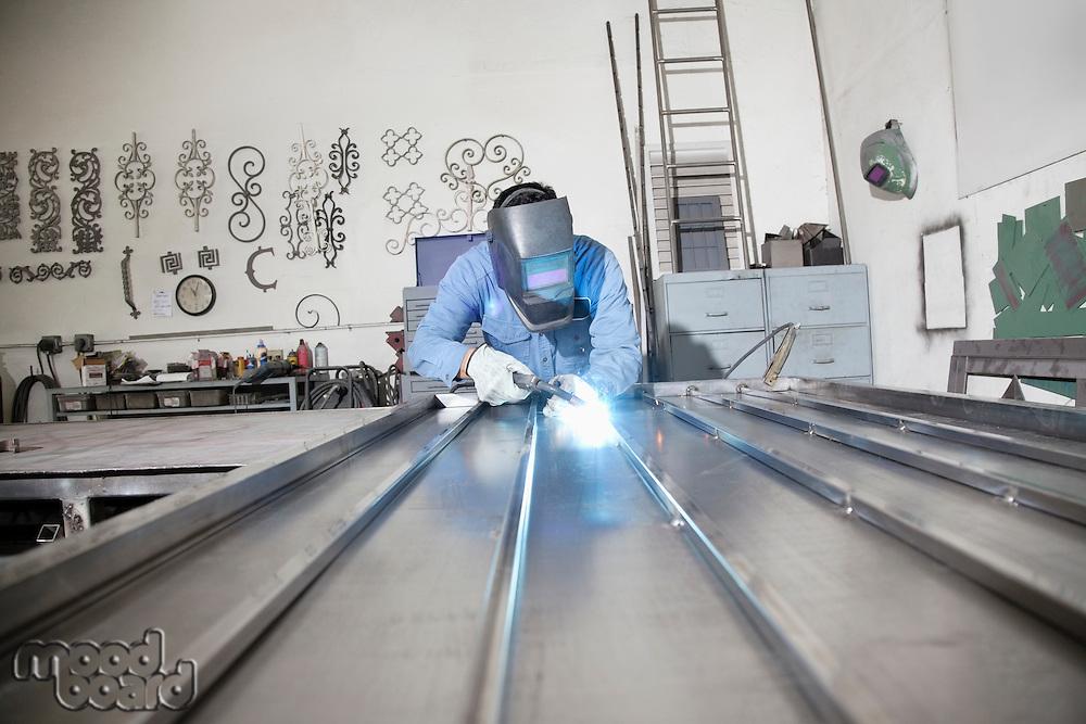 Young male worker welding in metal workshop