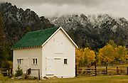 Seasons first snow dusts the Sawtooth mountains behind a barn during autumn in Atlanta, Idaho .