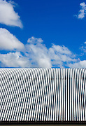 Blue sky and clouds over a corrugated tin roof <br />