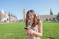 Young woman text messaging through smart phone against Big Ben at London; England; UK