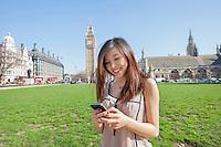 Young woman text messaging through smart phone against Big Ben at London; England; UK