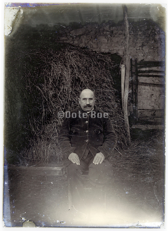 early 1900s farmer sitting by stacked hay on a eroding glass plate