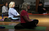 Middletown, New York - Women meditate at the end of a yoga class at the First Presbyterian Church on April 21, 2011.