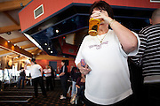 A large, manly woman sips a pint of lager during a darts tournament where she competes in an England Open tournament at the Bunn Leisure Holiday Park in Selsey, near Chichester on the south coast of England. Holding three darts with a Union Jack flags on the 'flights', her glass covers her face but we see her rings and bracelet and her ample belly after a life of beer and cigarettes in pubs like this. A great deal of alcohol (mostly lager, but also Coke) is consumed during darts tournaments although smoking in public places has now been banned in the UK, including pubs and bars. This audience seemed to consist largely of very large lesbian women from working families which seems to suggest that the pub (and alcohol) is still the place where women are attracted to the game of darts. ..