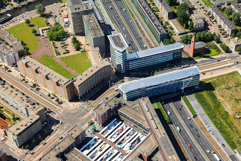 Nederland, Noord-Holland, Amsterdam, 14-06-2012; Bos en Lommer, Ring A10 - West met Poortgebouw. Hoofdweg,  markt op het Bos en Lommerplein. ..De wijk is onderdeel van de Westelijke Tuinsteden, gerealiseerd op basis van het Algemeen Uitbreidingsplan voor Amsterdam (AUP, 1935). Voorbeeld van het Nieuwe Bouwen, open bebouwing in stroken, langwerpige bouwblokken afgewisseld met groenstroken. ..Residential district Bos en Lommer (forest and foliage), one of the western garden cities of Amsterdam-west..  Constructed on the basis of the General Extension Plan for Amsterdam (AUP, 1935). Example of the New Building (het Nieuwe Bouwen), detached in strips, oblong housing blocks alternated with green areas, built in fifties and sixties of the 20th century. The church is nicknamed Kolenkit (coal-hod) and so this district is called the Coal-hod district. A10 Ringroad crosses the neighbourhood. .luchtfoto (toeslag), aerial photo (additional fee required).foto/photo Siebe Swart