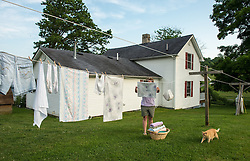 """Laundry hangs outside the home of Marilyn Mullens in Cool Ridge, West Virginia, where mountaintop-removal mines are abundant. Mountaintop Removal is a method of surface mining that literally removes the tops of mountains to get to the coal seams beneath. It is the most profitable mining technique available because it is performed quickly, cheaply and comes with hefty economic benefits for the mining companies, most of which are located out of state. Mullens organized the Memorial Day protest against mountaintop-removal mining: """"We just want people to be aware. Know that every time you turn on a light switch . . . someone here is paying for that with dirty water, with air that they can't breathe."""" © Ami Vitale"""