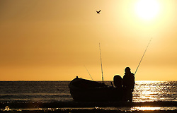 © Licensed to London News Pictures.12/06/15<br /> Saltburn by the Sea, England<br /> <br /> A crew member from the fishing boat Senna steadies the boat before heading out as dawn breaks over Saltburn by the Sea.<br /> <br /> Photo credit : Ian Forsyth/LNP