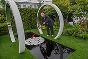 One of the builders puts finishing touches to the Breast Cancer now, throught the microscope garden - The Chelsea Flower Show organised by the Royal Horticultural Society with M&G as its MAIN sponsor for the final year.