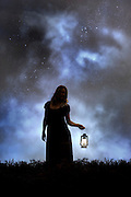 a woman in the dark with a lantern