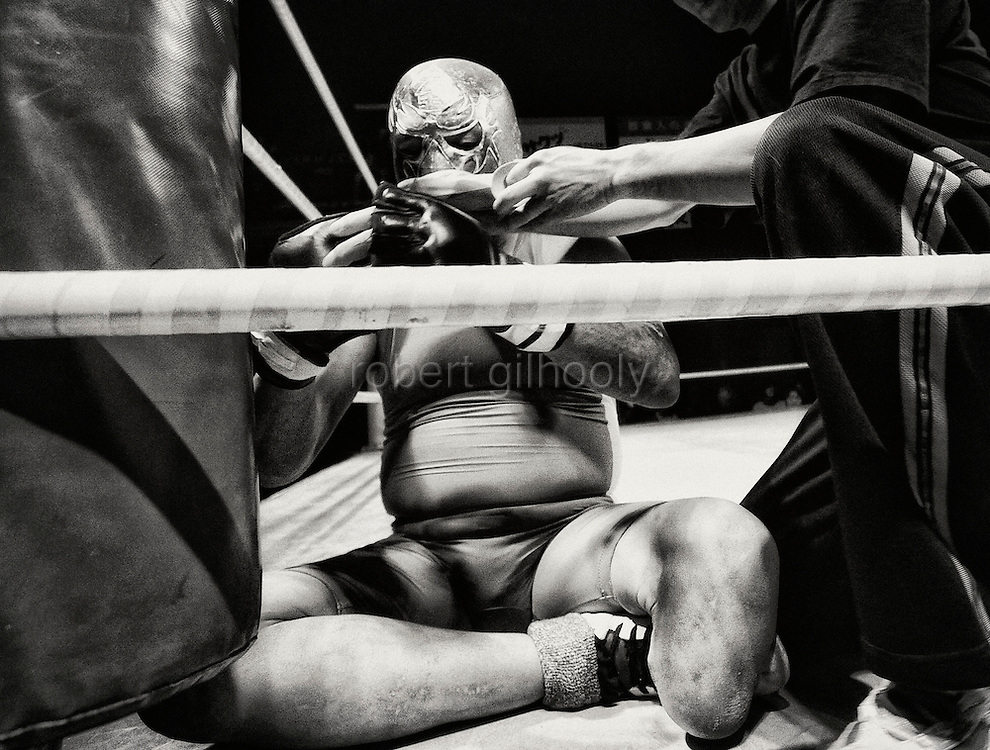A wrestler removes his gloves after bloodying his nose during a fight at Doglegs, an event for wrestlers with physical and mental handicaps in Tokyo, Japan.