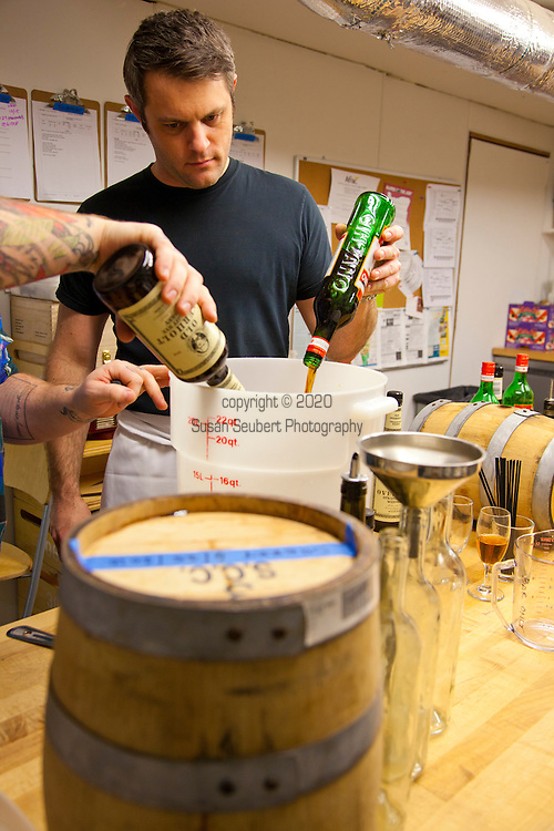 "Barrel-aged cocktails made by Clyde Common's restaurant bartender, Jeffery Morgenthaler, in Portland, Oregon.  Pictured here is Jeffery with his assistant, Junior Smith, preparing 2.5 gallons of ""Remember the Maine"" - a classic cocktail named after the USS Maine which sank in the Havana harbor in 1898, the event which precipitated the Spanish-American War.  The drink consists of Rye Whiskey, Sweet Vermouth, Cheery Heering and Absinthe."