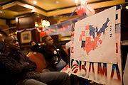 With a hand-drawn map of the United States coloured in increasingly in blue, American expatriates of African-american ethnicity sit and watch live BBC and SKY News TV screen that is broadcasting live the latest polls of the 2008 US presidential elections. Early polls suggest Barack Obama is doing well against his Republican adversary, John McCain in this historic political election which saw the election of America's first black Commander in chief. The location is a pub called the Hoop and Toy, in South Kensington, West London which has been opened all night for this special event for the American expatriate community living in this European capital.