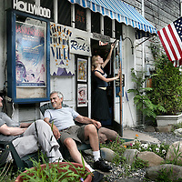 Verenigde Staten.Piermont.New York State.Rockland. 8 juli 2005.<br /> Buurtbewoners uit het plaatsje Piermont rusten in het centrum even uit bij de locale videotheek Rick's Piermont picture video.Amerikaanse vlag.Nationale trots.Filmposters.Ontspanning.recreatie.Genieten.Oude dag.Veranda.<br /> Archives 2005, in the streets of Piermont, New York USA.