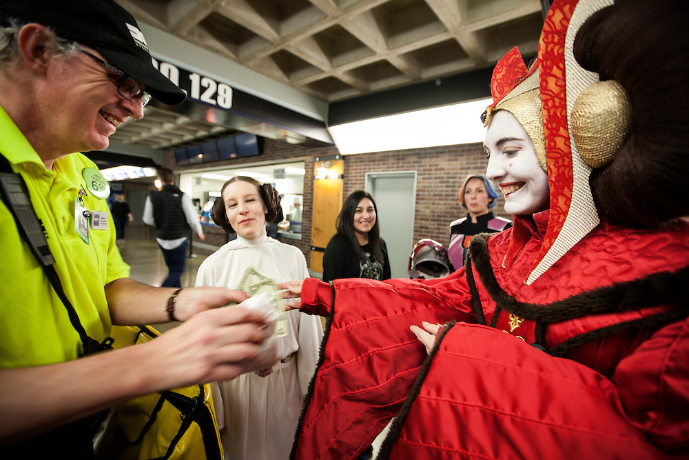 Queen Amidala (Jo O'Hanley), right, purchases a bag of mini donuts as Princess Leia (Lynn Sessions) looks on during Star Wars night at the Timberwolves game at Target Center in Minneapolis December 15, 2015.