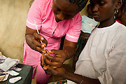 MCH aide Aminata Kamara collects a blood sample to test a pregnant woman for HIV at an outreach clinic for women and children under five in the village of Kobotu, Sierra Leone on Friday April 23, 2010. The outreach clinic takes place twice a month, and health workers come from the PHU where they normally work, 5 km away.