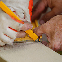 Adam Robison   BUY AT PHOTOS.DJOURNAL.COM<br /> Workers mark their cut on a piece of siding.