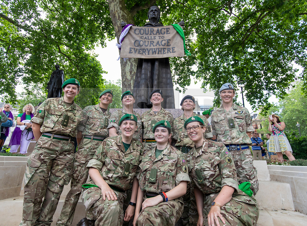 © Licensed to London News Pictures. 10/06/2018. London, UK. Women serving in the Armed Forces pose in front of the Millicent Fawcett statue in Parliament Square as thousands of people march through central London wearing green, white and violet, the colours of the Suffragette movement,  to celebrate 100 years votes for women. Photo credit: Rob Pinney/LNP