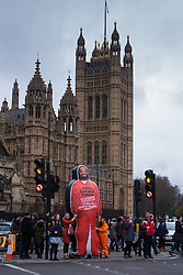 London, February 14th 2015. Dozens of orange boiler-suit clad protesters march from Parliament Square to Downing Street in protest against the ongoing detention in Guantanamo Bay of British subject Shaker Amer, who has been held without charge for 13 years. PICTURED: A 10 foot-tall inflatable effigy of Shaker Amer arrives at the protest.