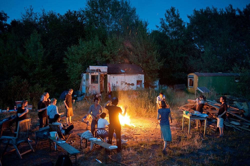"""Die Bewohner haben Freunde und<br /> Bekannte zum Abendessen eingeladen (links). Den neuen Schuppen mit dem<br /> Wellblechdach nennen hier alle nur """"die Aussenküche"""", dort gibt es auch einen<br /> großen KÜHLSCHRANK. Den Schuppen haben die Bewohner erst vor<br /> Kurzem innerhalb eines Wochenendes zusammengezimmert. Handwerkliches<br /> Geschick ist generell wichtig für das Leben im Bauwagen. Viele haben an<br /> ihren rollenden Wohnungen jahrelang gebaut, im Internet tauschen sich<br /> Wagenfreaks über Bautipps und die richtige Isolierung aus"""
