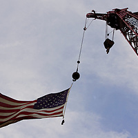 Construction crane flying an American Flag at the end of its mast. The Highlands-Sea Bright Bridge is a 1,240-foot drawbridge, built in 1932, to connect Highlands, New Jersey in the west to Sea Bright, New Jersey in the east, across the Shrewsbury River. The eastern terminus is at the entrance to Sandy Hook. The span is part of Route 36.  The bridge is being replaced with a fixed span instead of a drawbridge. It will rise 65 feet instead of the original spans 35 feet.  The construction project is expected to be completed in 2012