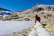 Hiker legs resting by iced lake in Sierra de Gredos (Spain)
