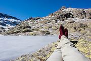 Hiker legs resting by iced lake in Sierra de Gredos (Spain)