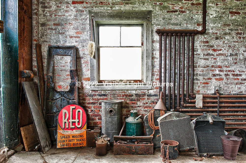 Garage / barn at the Hancock Shaker Village in MA.  Along with a vintage REO vehicle behind me, these old car parts and sign are part of the clutter in what seemed to be an abandoned side of the garage.